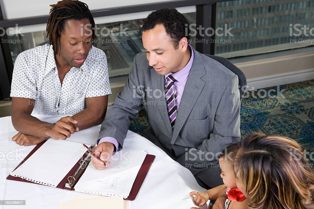 Family discussing college at a table with financial planner stock photo