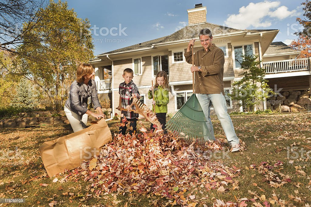 Family Doing Autumn Outdoor Leave Raking Work Together stock photo