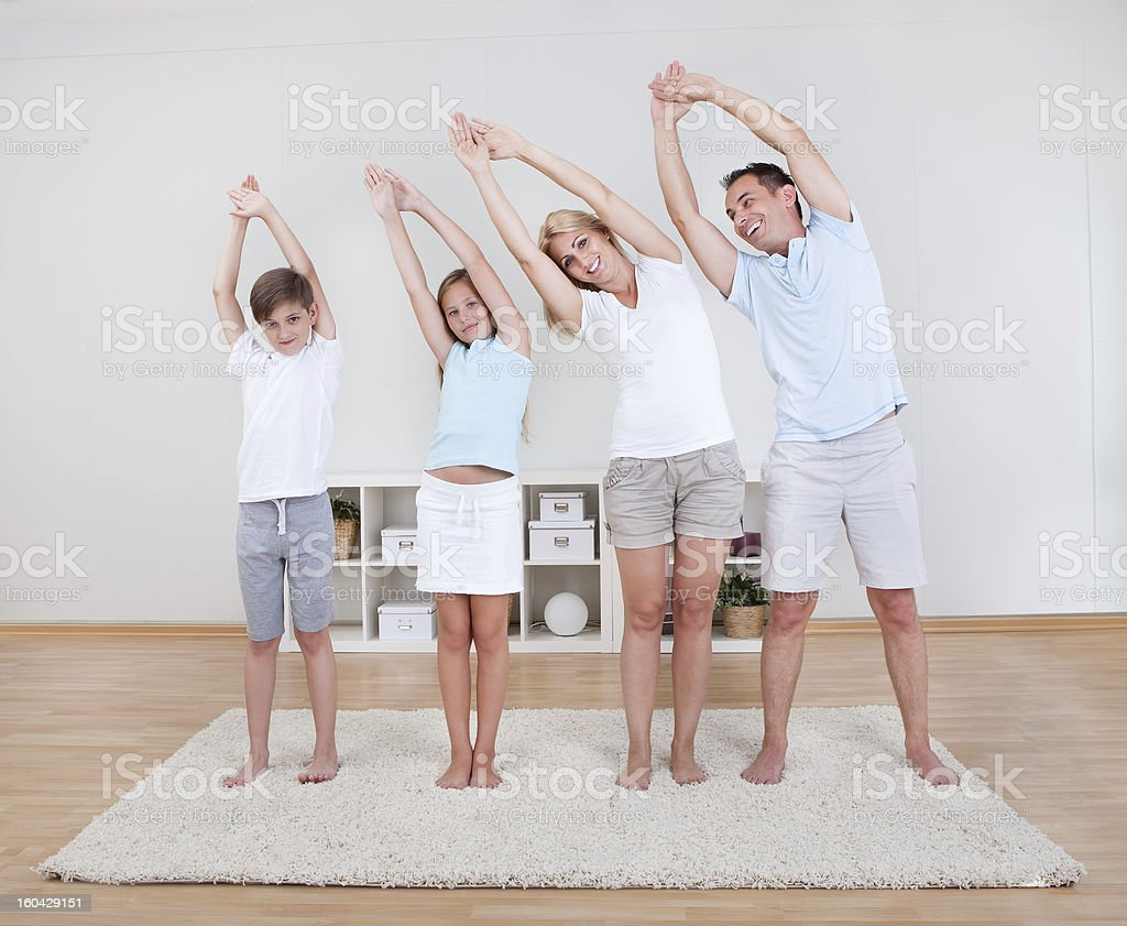 Family Doing Stretching Exercises On The Carpet stock photo