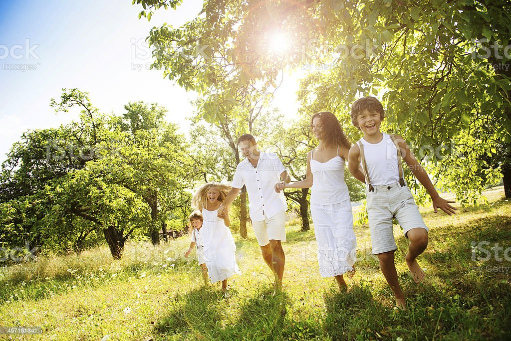 Family dressed in white walking in forest on sunny day stock photo