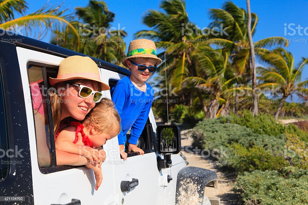 Family driving an off-road car on tropical beach with palms stock photo