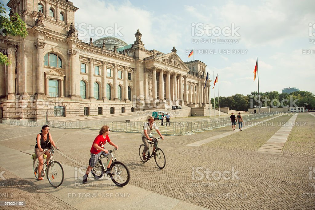 Family driving by cycles around Reichstag building stock photo