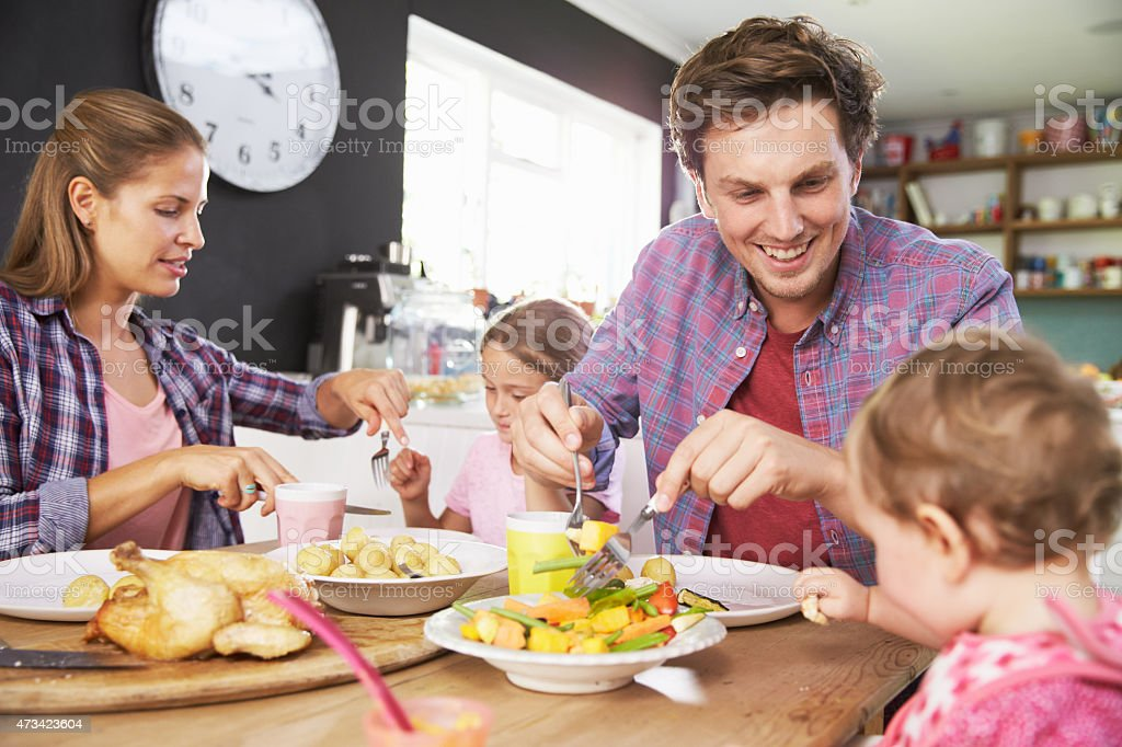 A family eating a meal together in the kitchen stock photo