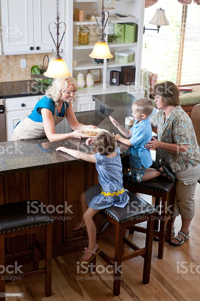 Family eating cookies in the kitchen stock photo