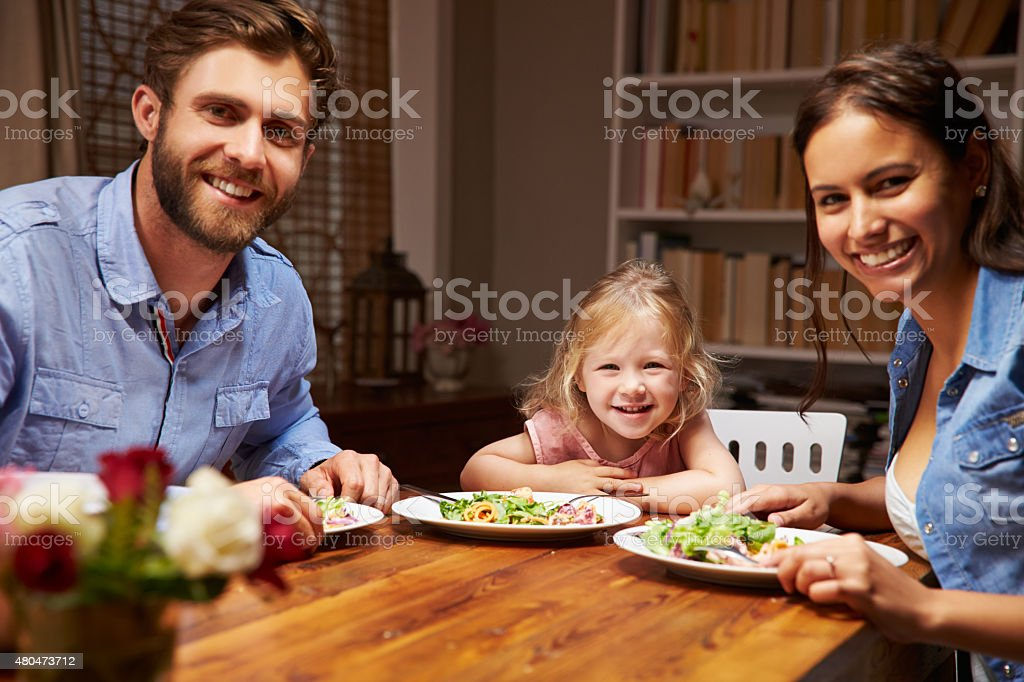 Family eating dinner at a dining table, looking at camera stock photo