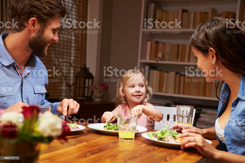 Family eating dinner at a dining table stock photo