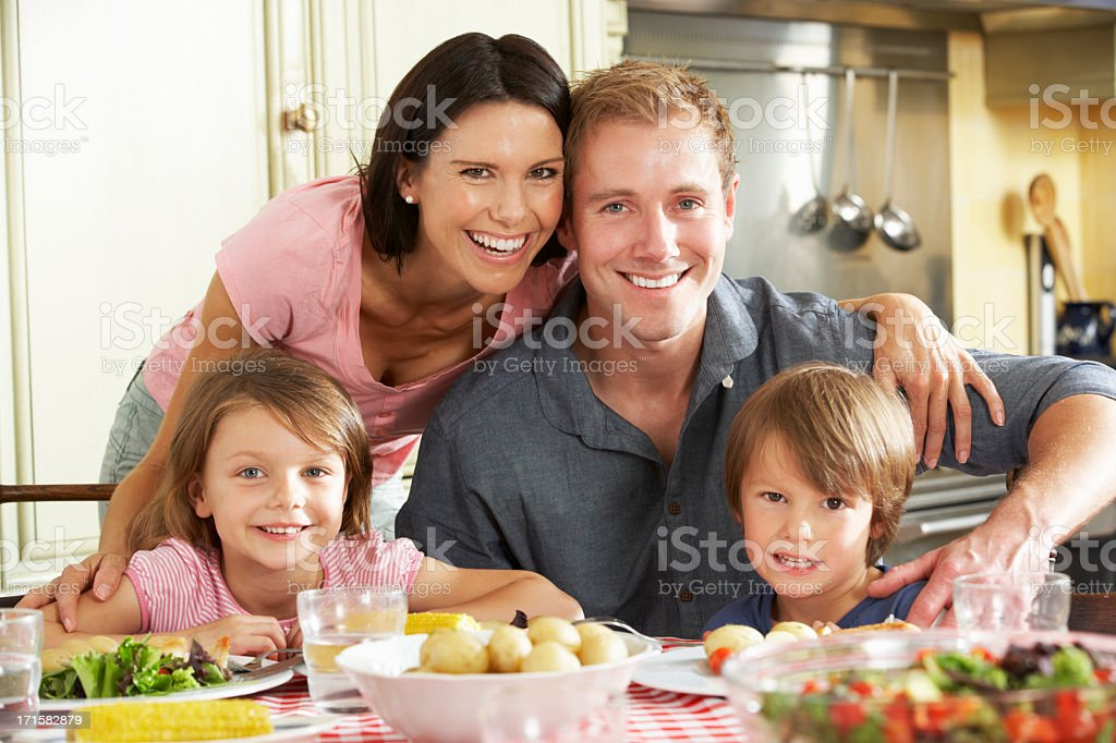 A family eating food at the kitchen tables royalty-free stock photo
