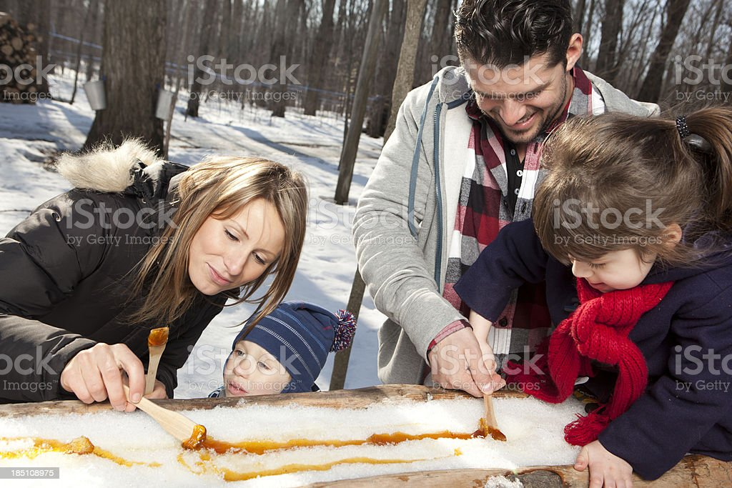 Family eating maple taffy on sticks stock photo