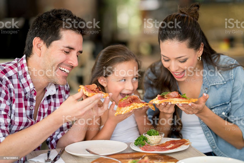 Family eating pizza at a restaurant stock photo