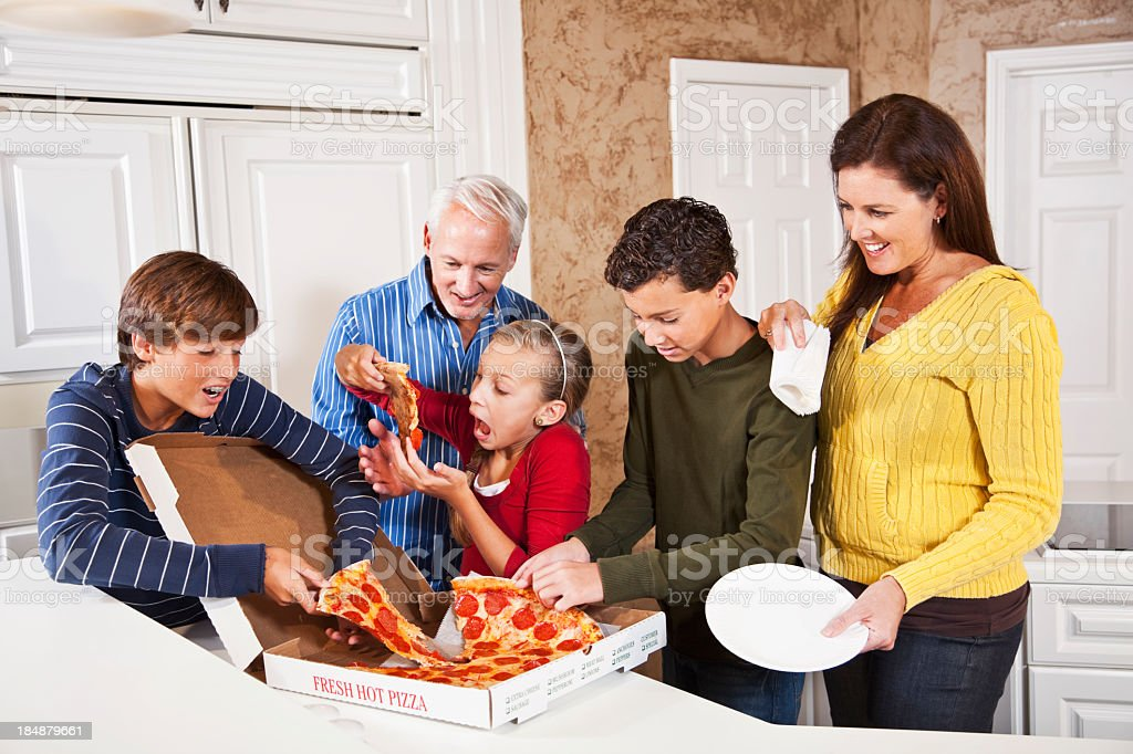 Family eating pizza from take-out box royalty-free stock photo