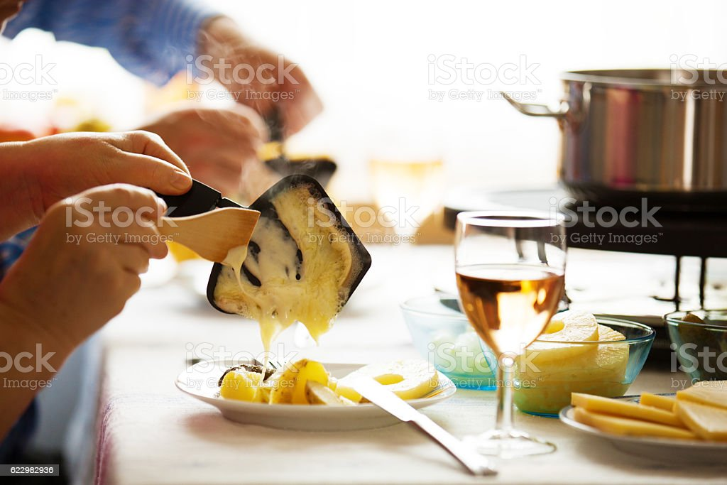 Family eating raclette. Close up concept. stock photo