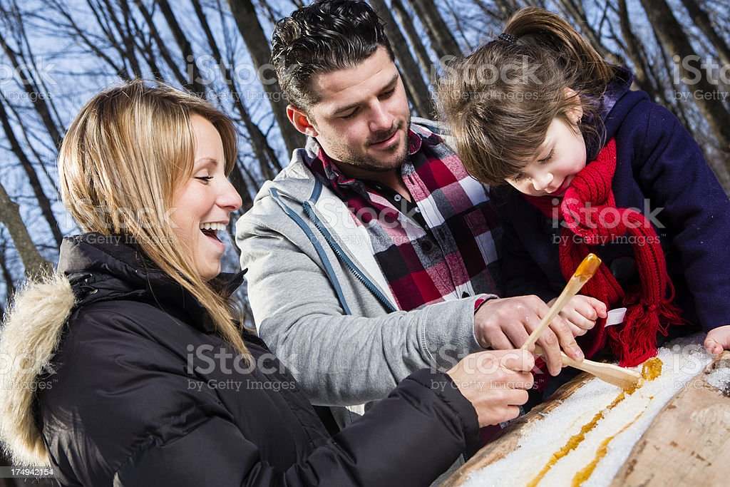 Family eating sap on snow stock photo