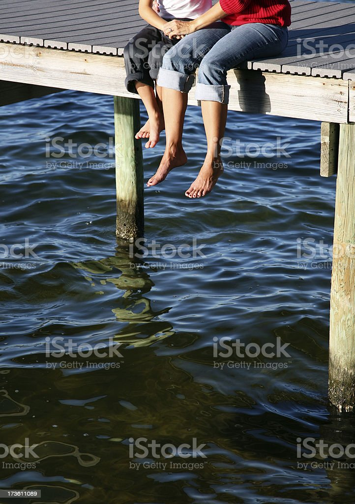 Family Embrace Sitting on a Dock at the Bay royalty-free stock photo