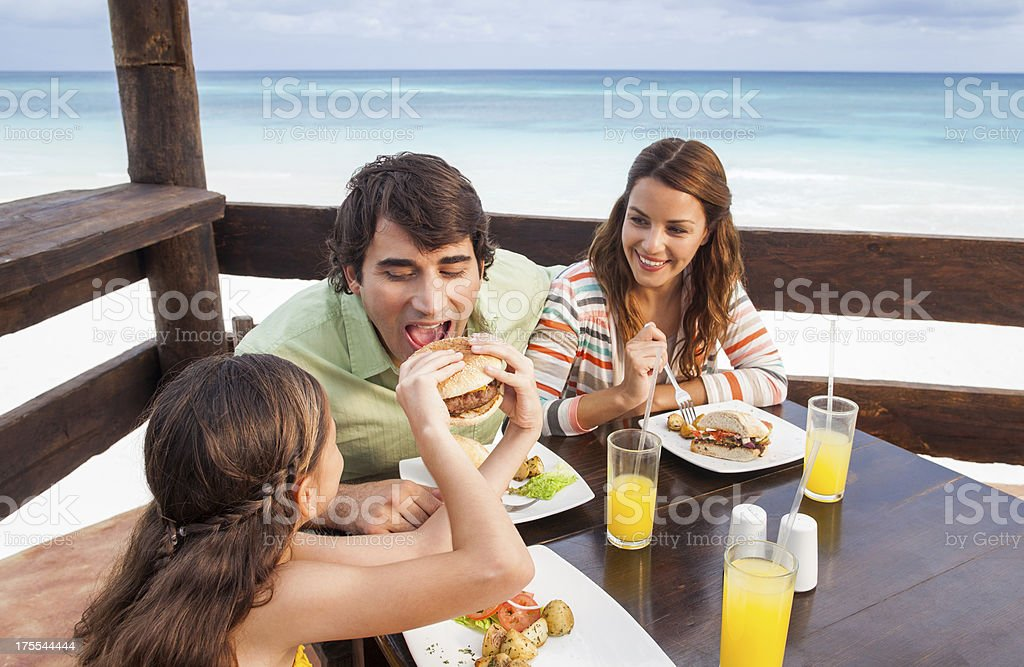 Family enjoying a meal at the beach royalty-free stock photo