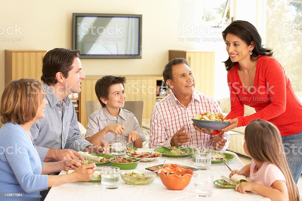 Family enjoying a meal at the table with green plates stock photo