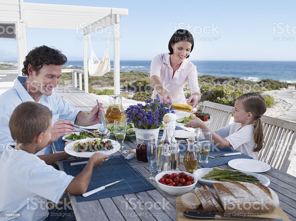 Family enjoying a meal outdoors on their terrace royalty-free stock photo
