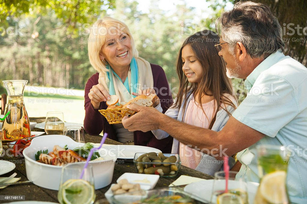 Family enjoying barbecue at outdoors stock photo