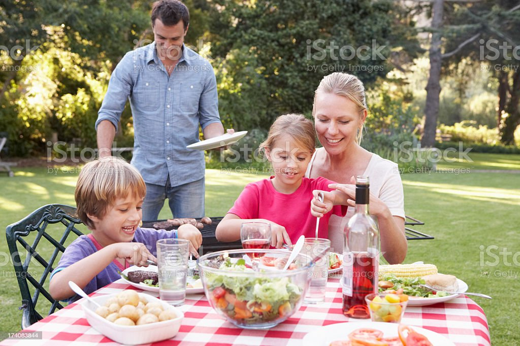 Family Enjoying Barbeque In Garden royalty-free stock photo