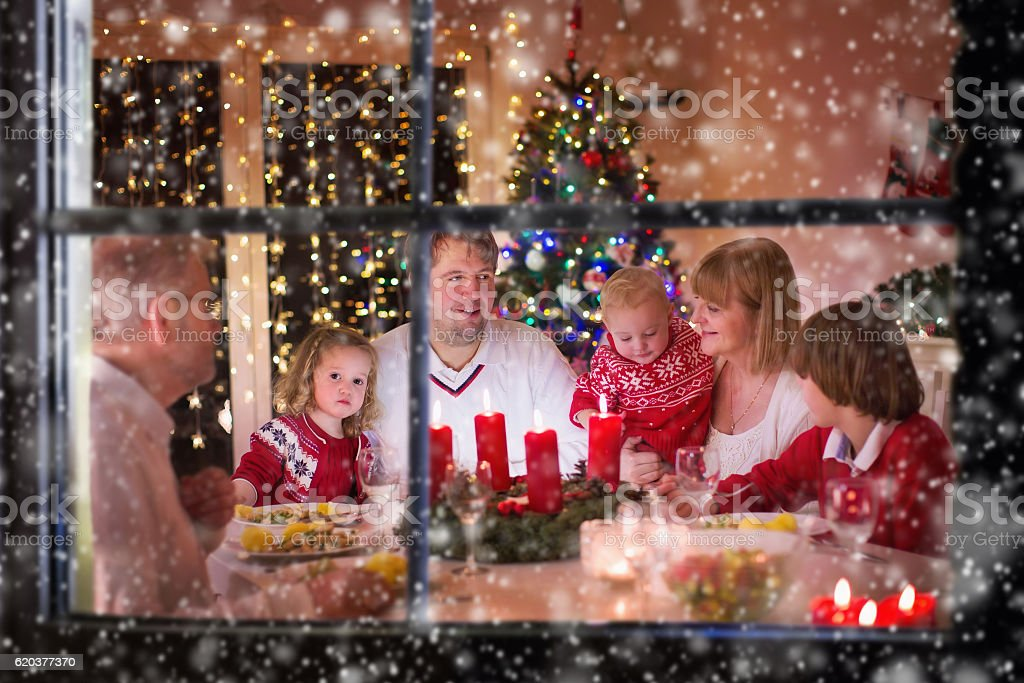 Family enjoying Christmas dinner at home in decorated room stock photo