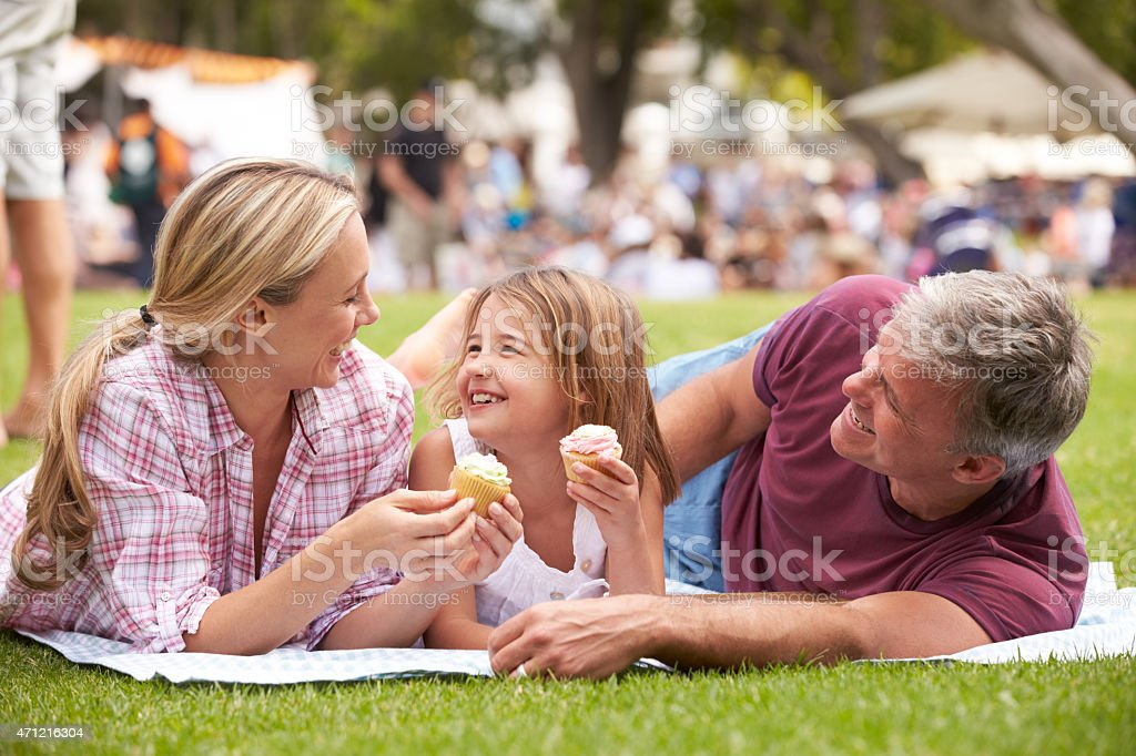 Family Enjoying Cupcakes At Outdoor Summer Event stock photo