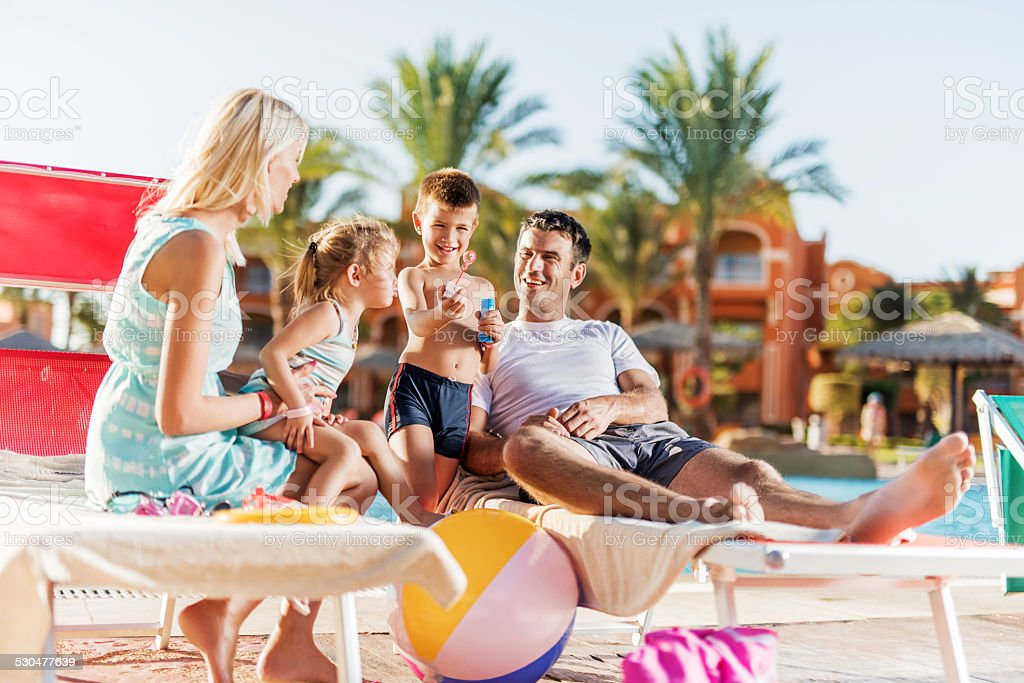Family enjoying in summer day at poolside. stock photo