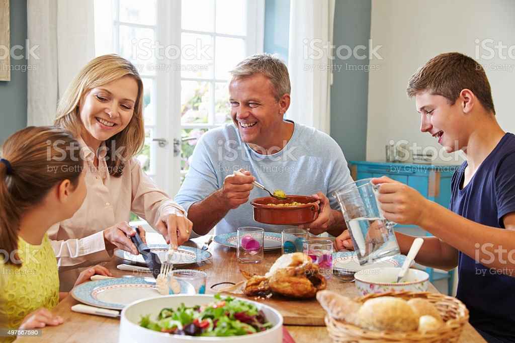 Family Enjoying Meal At Home Together stock photo
