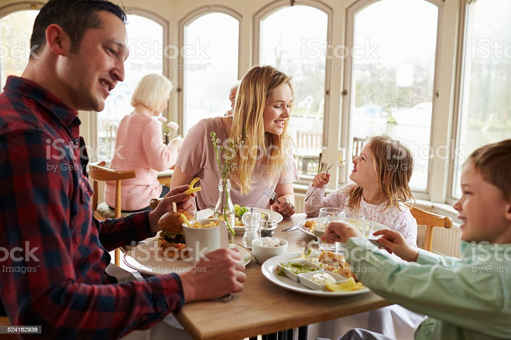 Family Enjoying Meal In Restaurant Together stock photo