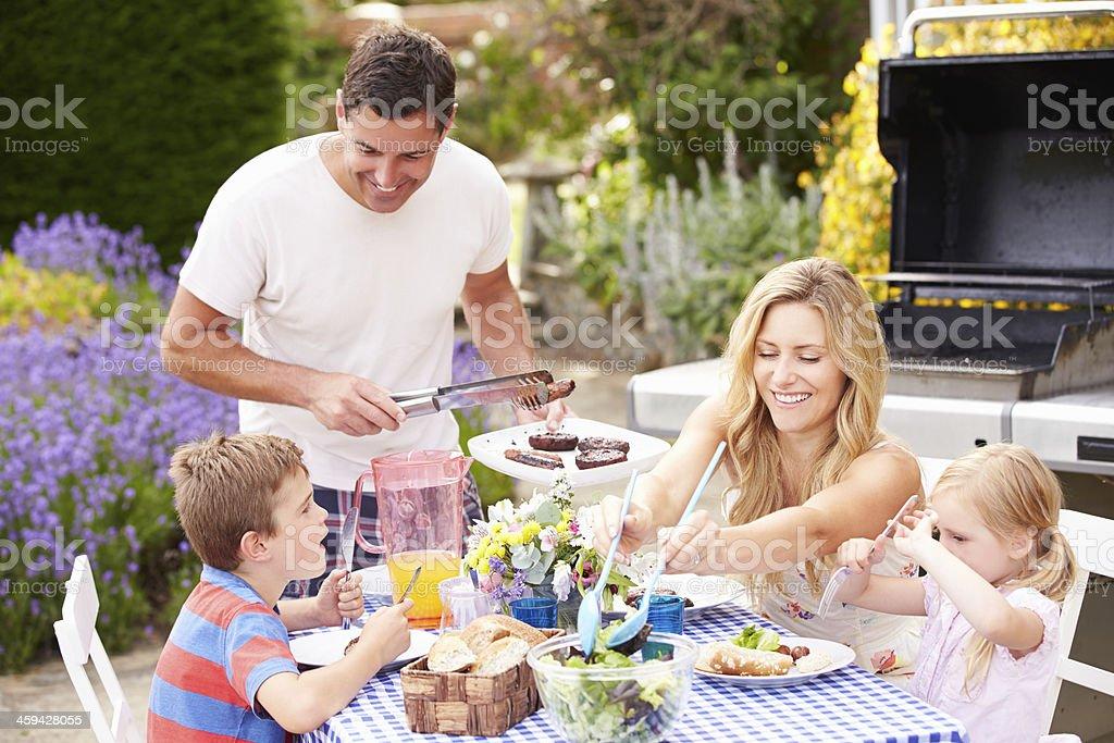 Family Enjoying Outdoor Barbeque In Garden stock photo