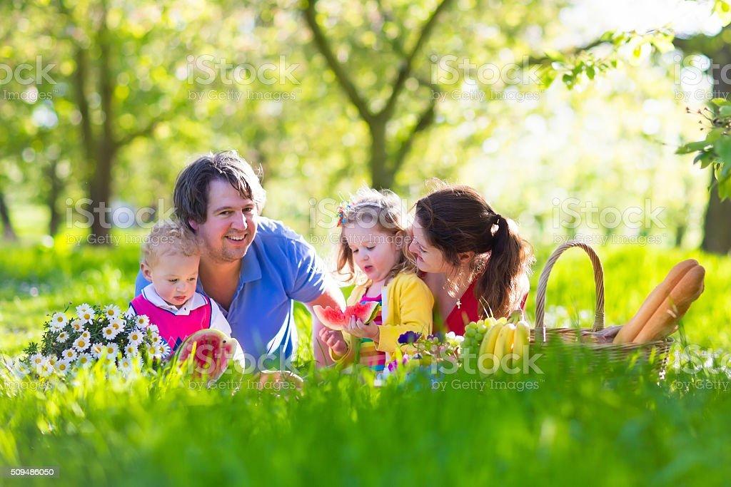 Family enjoying picnic in blooming garden stock photo