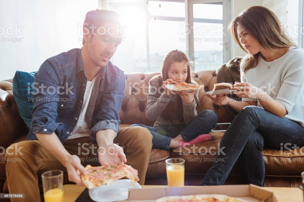 family enjoying pizza for lunch stock photo