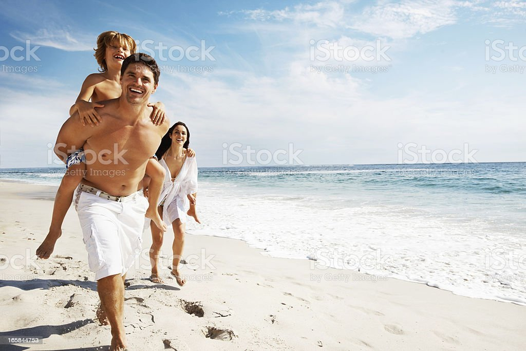 Family enjoying their summer vacation on the beach royalty-free stock photo