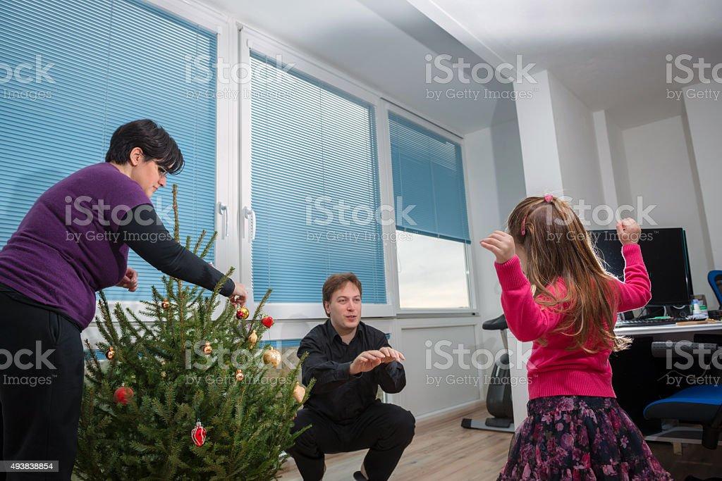 Family Enjoying while Decorating Christmas Tree, Europe stock photo