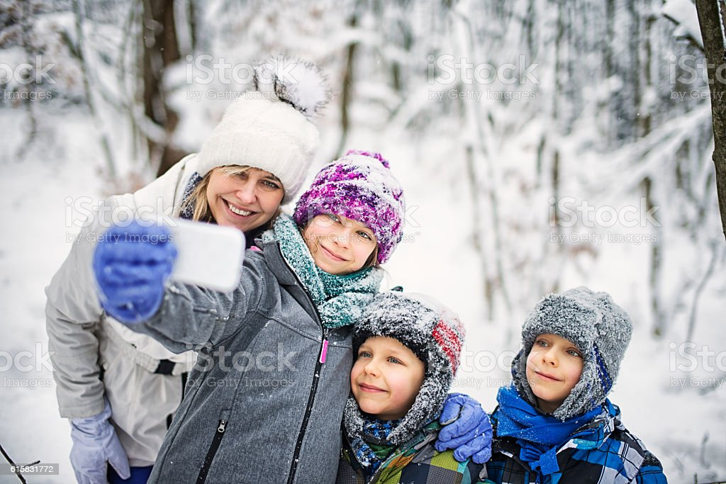 Family enjoying winter walk in forest. stock photo