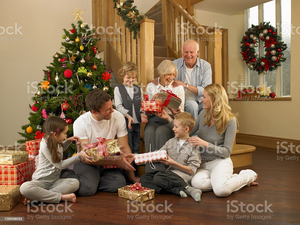 Family Exchanging Gifts In Front Of Christmas Tree royalty-free stock photo