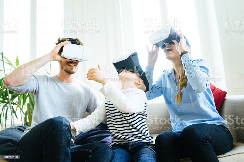 Family Experiencing Virtual Reality And Having Fan At Home stock photo