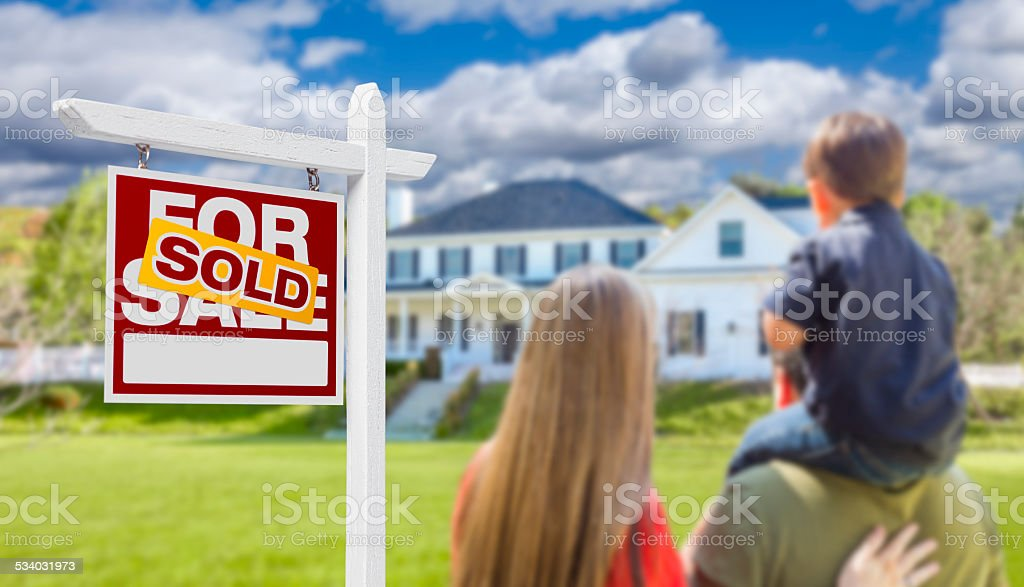 Family Facing Sold For Sale Real Estate Sign and House stock photo