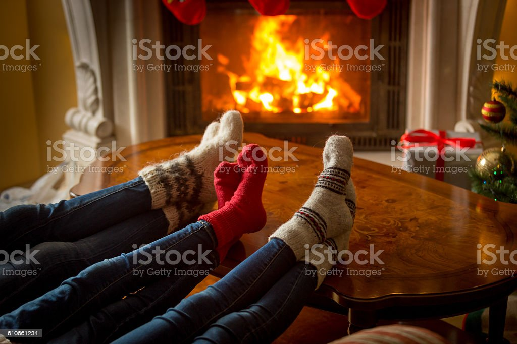 Family feet in socks resting next to the burning fireplace stock photo