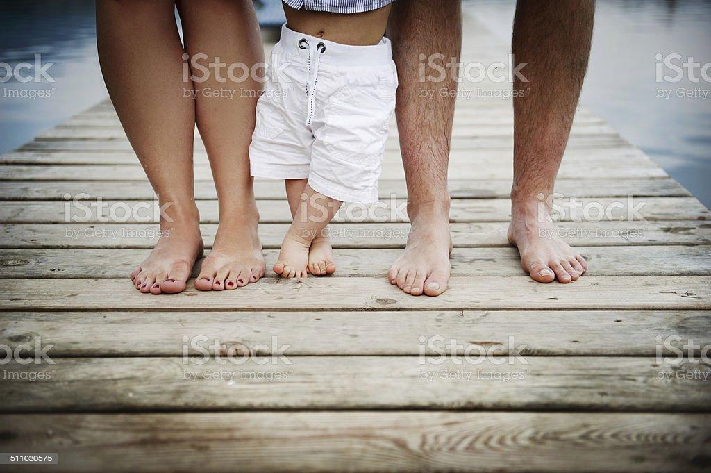 Family feet on pier stock photo