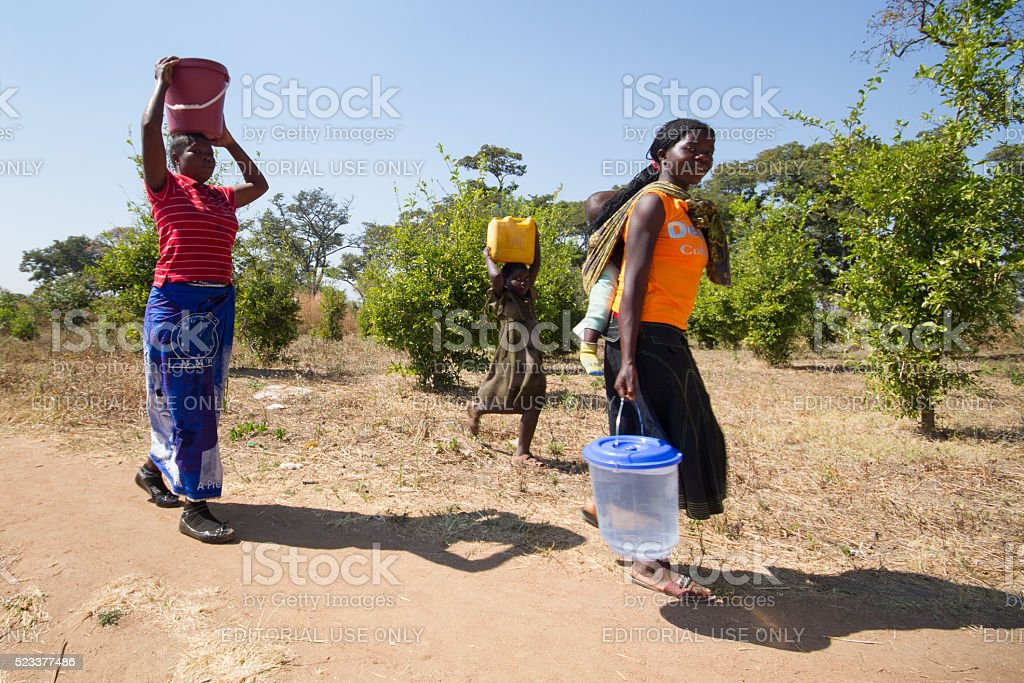 Family fetching water with buckets in rural Southern Africa. stock photo