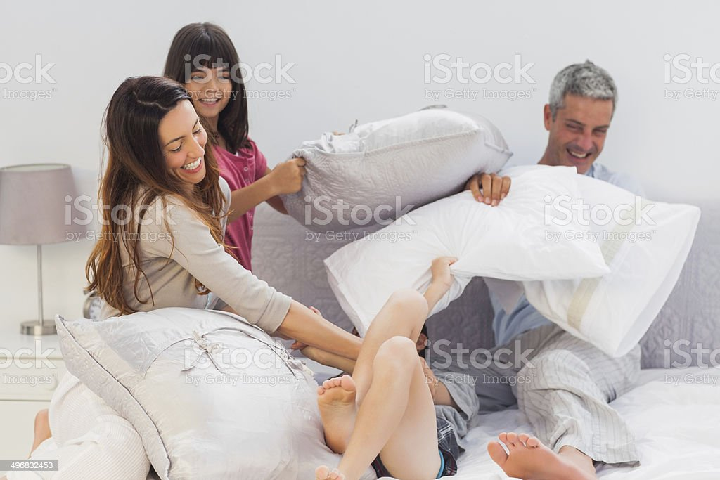 Family fighting together with pillows on bed stock photo