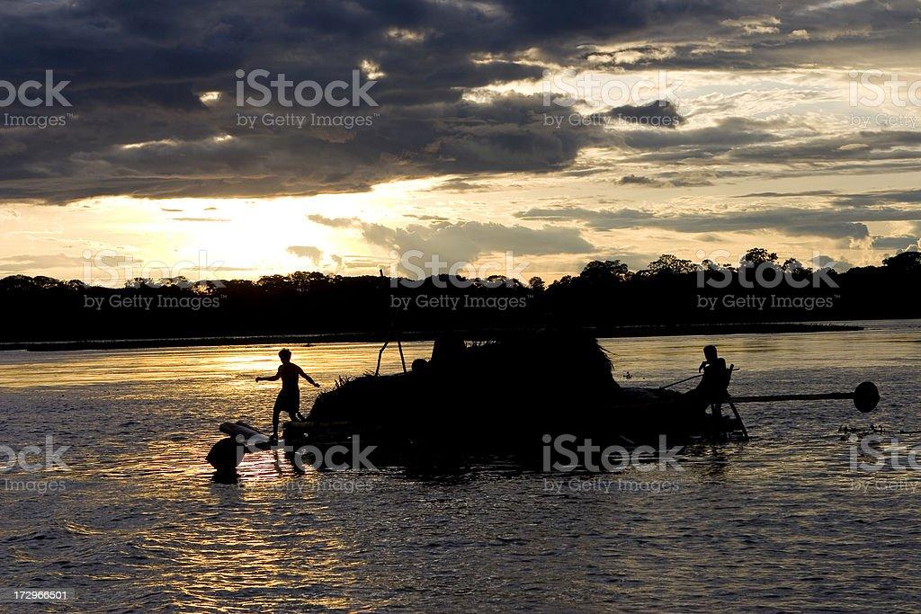 'Family floats down Amazon River on raft, Peru' stock photo