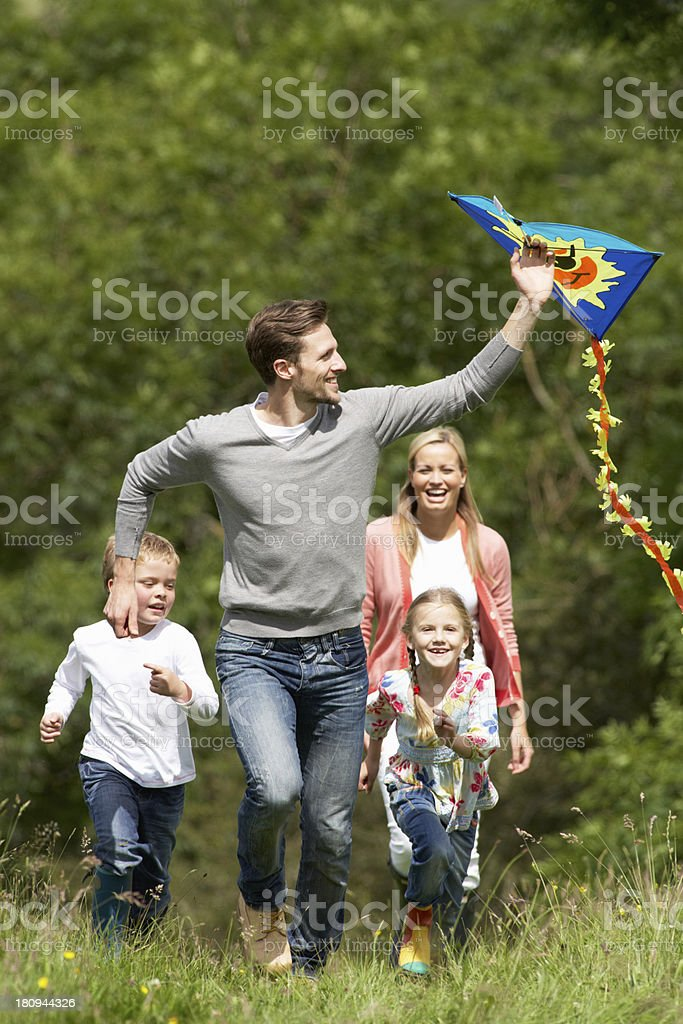 Family Flying Kite In Countryside stock photo