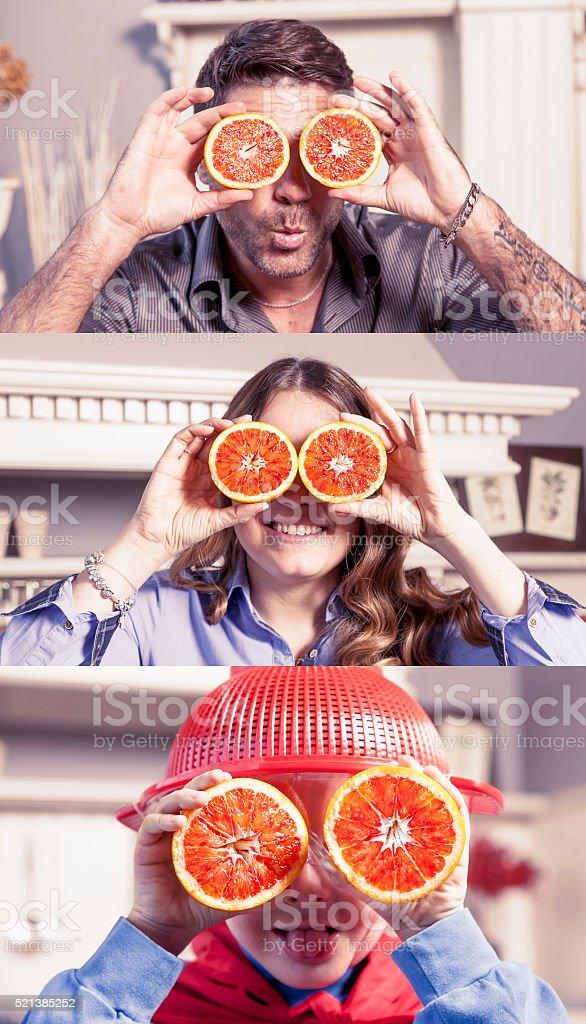 family fun putting oranges on the eyes stock photo