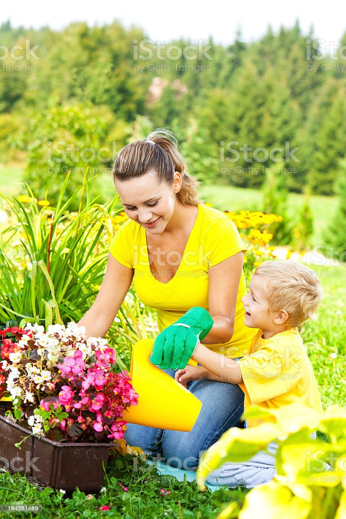 Family Gardening: Mother And Child Watering Flowers royalty-free stock photo