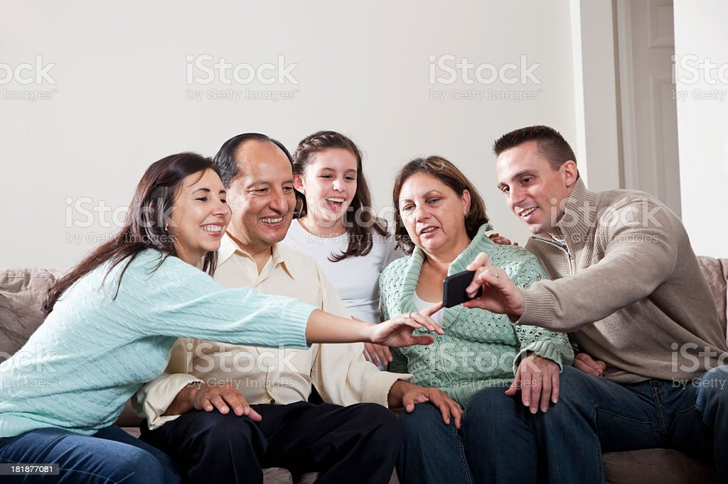 Family gathered around mobile phone stock photo