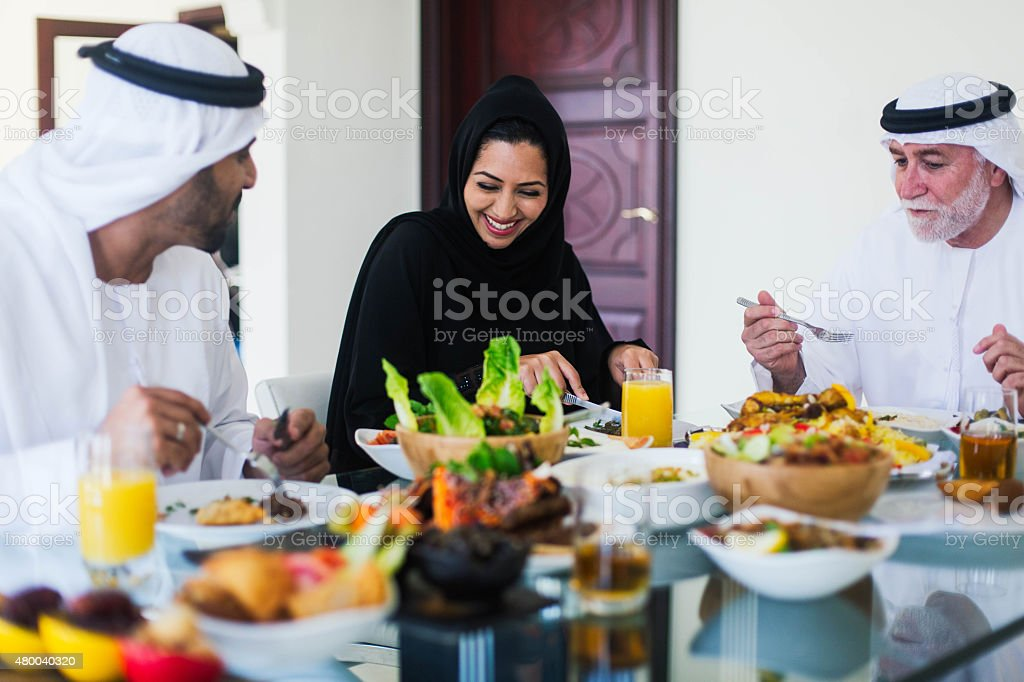 Family gathering, three generations eating traditional food. stock photo