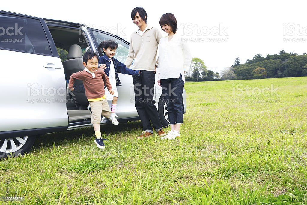 Family getting off a car in prairie stock photo