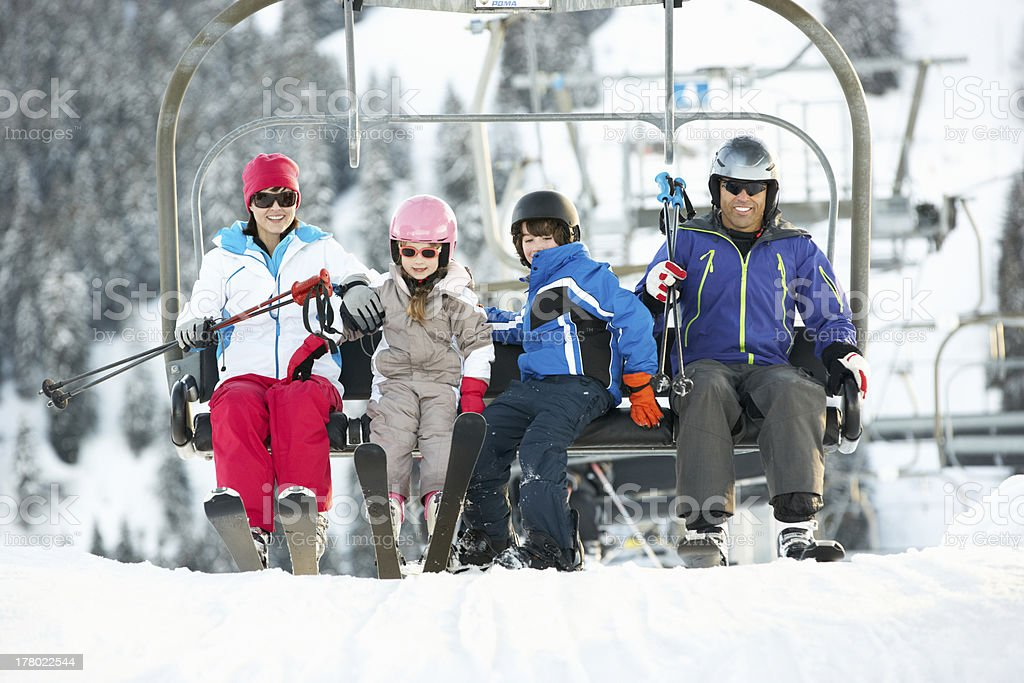 Family Getting Off chair Lift On Ski Holiday In Mountains stock photo