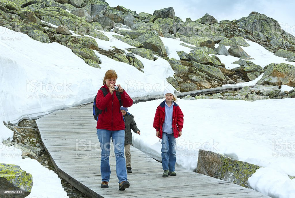 Family going on wooden flooring (Bettmerhorn, Switzerland). stock photo