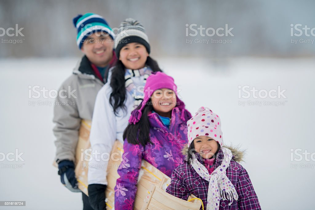 Family Going Tobogganing Together stock photo